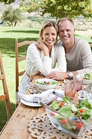 Portrait of smiling couple enjoying lunch at table in garden