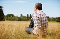 Pensive man sitting in rural field