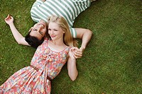 Young couple laying in grass and holding hands