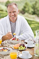 Portrait of smiling man eating breakfast at patio table