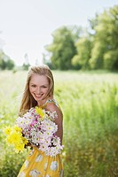 Smiling woman with flowers in rural field