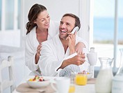 Happy couple in bathrobes talking on telephone at breakfast table