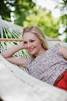 Smiling woman laying in hammock and listening to music on headphones