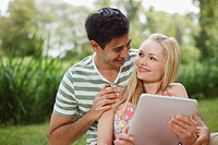 Young couple using digital tablet in park
