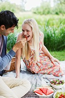 Man feeding woman strawberry on picnic blanket in park