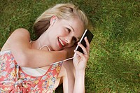 Smiling woman listening to music on headphones and looking at mp3 player