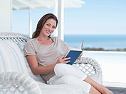 Portrait of smiling woman reading book on patio overlooking ocean