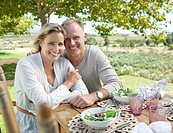 Portrait of smiling couple enjoying lunch at table in rural field
