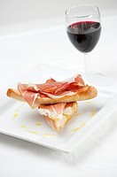 Iberian ham with bread and a glass of red wine - Tapas food
