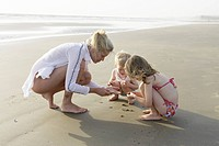 Mother and children playing on beach