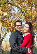 Couple smiling under fall leaves
