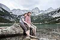 Smiling couple dangling feet in lake