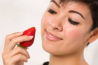 Pretty Hispanic Woman Holding Strawberry