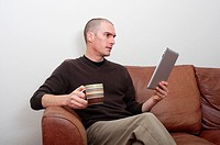 forty year old man using ipad tablet in casual setting