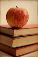 Three old books with a red apple. Slight textured finish