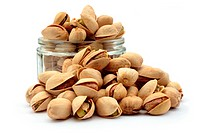 many pistachio nuts and a glass container. Isolated on a white background