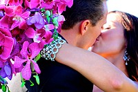 bride groom embracing with bouquet kissing  after wedding