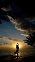 A young women practises the art of Yoga over a beautiful sunset at Tenerife beach