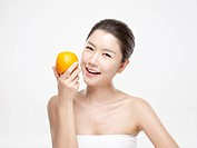 Close_up portrait of young woman holding orange