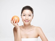 Close_up portrait of young woman holding grapefruit