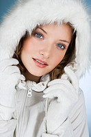 A young woman wearing a winter coat with a fur hood , close_up