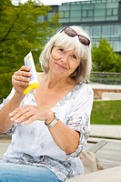 Elderly lady applying sunscreen agent