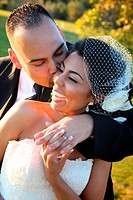 bride and groom embracing kissing smiling happy on wedding day