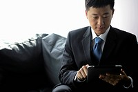 Young man in suit working on a tablet