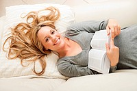 Happy young woman lying with book