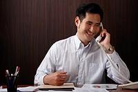 man sitting at desk talking on phone