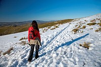 woman with rucksack on snow path