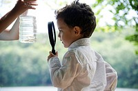Boy studying fish in water bottle with magnifying glass