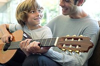 Boy learning how to play guitar with father