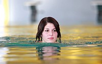 Young woman is swimming in the indoor swimming pool