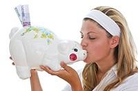 Young woman kisses piggy bank