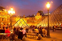 Sitting in a cafe in Cour Napoleon by the Pyramide and Musee du Louvre in Paris at night, France