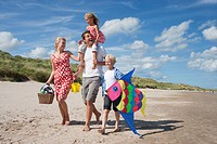 Family with picnic basket and kite walking on sunny beach