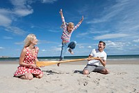 Girl jumping over paddle held by parents on sunny beach