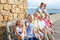 Portrait of smiling family sitting near ocean