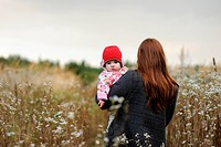 Young mother walking away holding her baby
