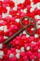 Old brass key on candy hearts