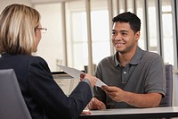 Businesswoman handing paper to co_worker