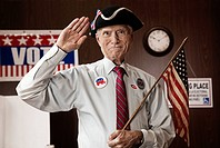 Caucasian man holding American flag in polling place
