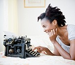 Black woman using old_fashioned typewriter