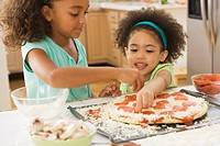 Mixed race sisters making pizza