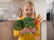 Caucasian girl holding carrots and broccoli
