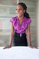 Black businesswoman reviewing blueprints