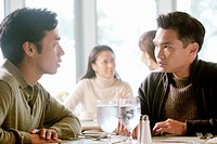 Asian men talking in restaurant