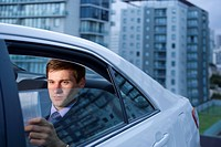 Caucasian businessman reading in back seat of car
