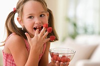 Girl eating raspberries from fingers
